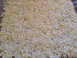Blumenkohl und Eier mit 150 Gramm geriebenem Käse (ich habe Gouda genommen) vermengen und auf ein Backblech (mit gutem, festen Backpapier) verteilen. Bei 180° im Ofen gute 20 Minuten vorbacken.